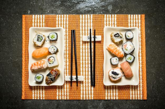 Суши и роллы с морепродуктами на бамбуковой подставке.