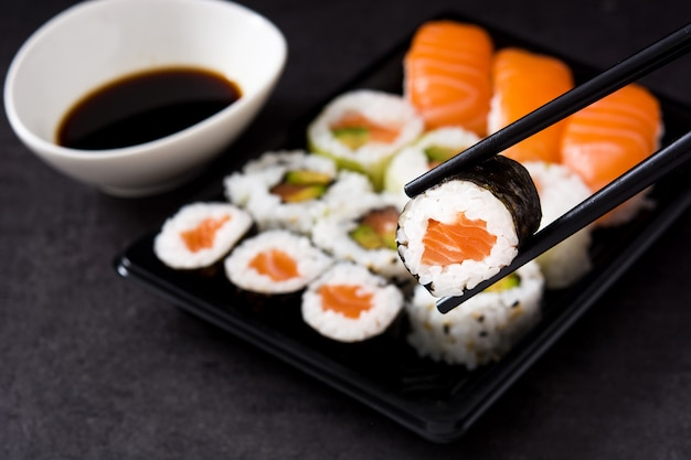 Sushi assortment on black tray and soy sauce.