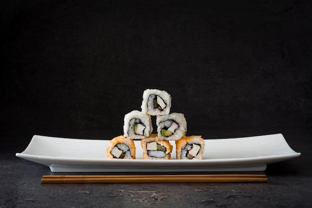 Ассортимент суши на белой тарелке на черном