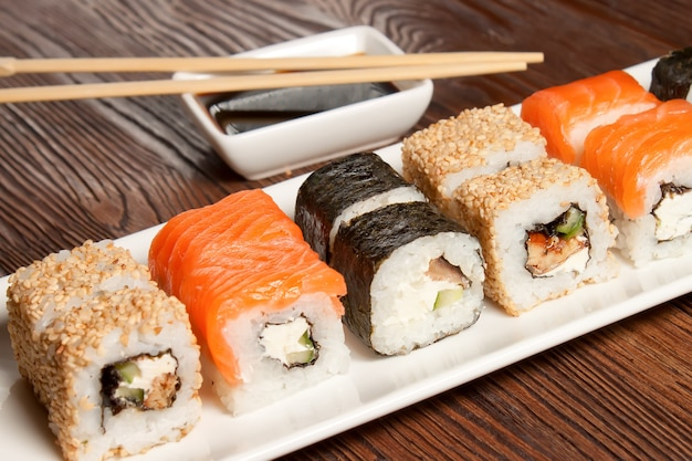 Sushi assortment on white dish on brown wooden table