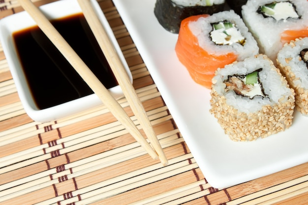Sushi assortment on white plate, with soy sauce over bamboo background.