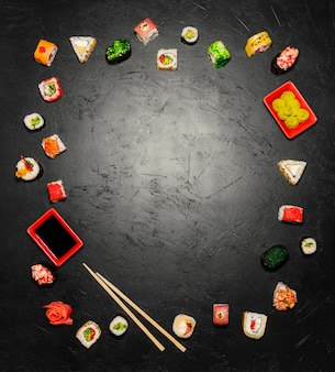 Sushi background. Top view of Japanese Sushi and chopsticks on black background