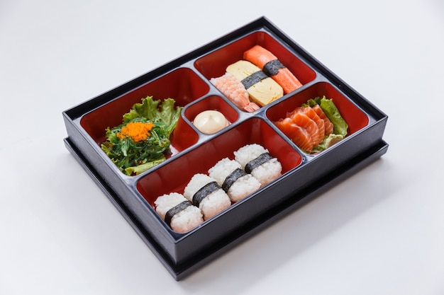 Sushi bento including rice wrap with seaweed.