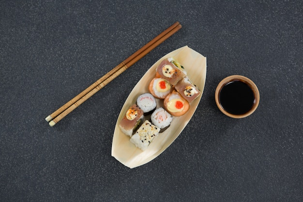 Sushi on boat shaped plate with chopsticks