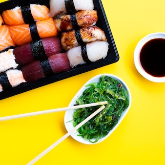 Sushi box plate with seaweed salad and soy sauce on yellow background