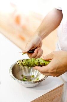 신선한 와사비를 뿌린 초밥 요리사, 신선한 와사비 뿌리는 초밥 초밥을 준비합니다.