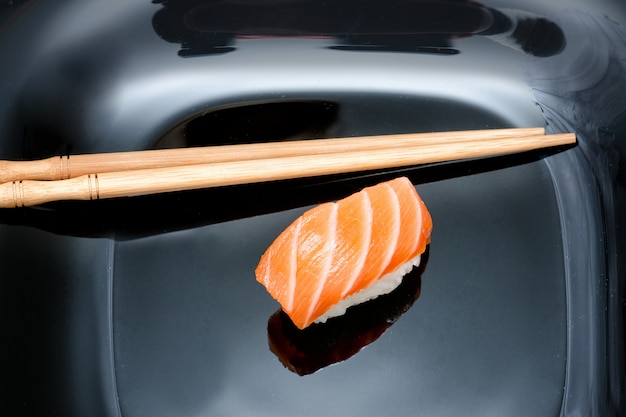 Sushi and chopsticks on black plate.