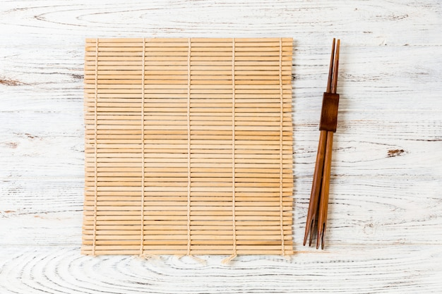 Sushi chopsticks with empty brown bamboo mat