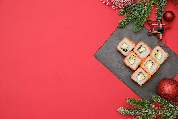 Sushi for christmas concept. edible christmas tree made from philadelphia roll on red background with decorations
