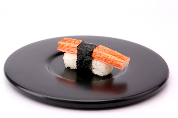 Sushi crab sticks with a black plate on a white background.