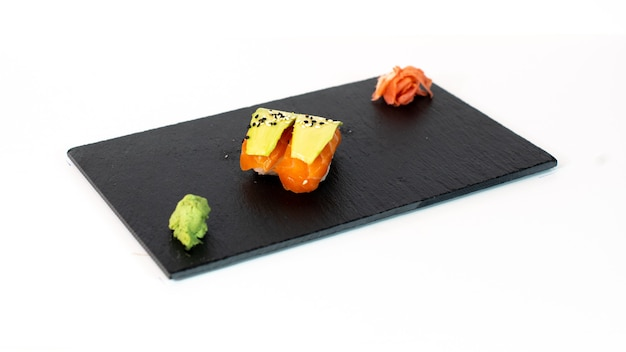Sushi de salmón con con aguacate sobre tabla negra