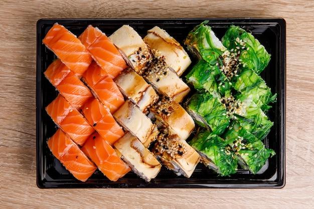 초밥 배달. 검은 플라스틱 포장에 다른 롤 상위 뷰 작성. 일본과 아시아 음식.