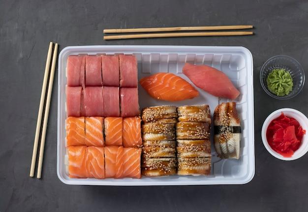 Доставка суши. одноразовая коробка для еды с суши-роллами, васаби, имбирем и палочками для еды на темной поверхности. сашими. лосось. тунец. угорь. японская еда на вынос. вид сверху