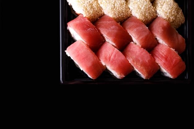 Доставка суши. набор рулонов в одноразовой коробке на черном фоне.