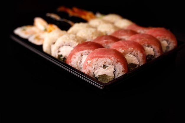 Доставка суши. набор рулонов в одноразовой коробке на черной поверхности.