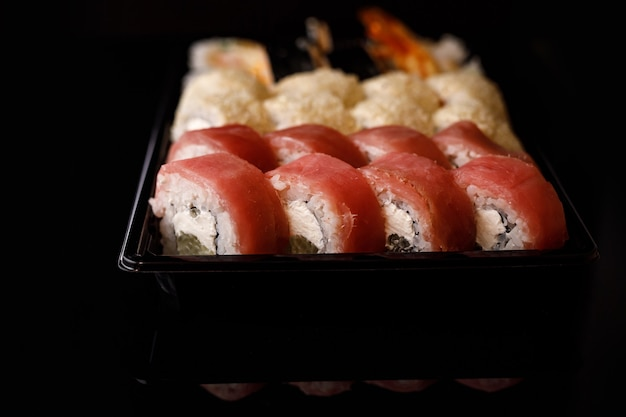 Sushi delivery. set of rolls in a disposable box on a black surface.