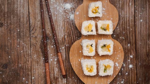 寿司の配達。ご飯、パイナップル、キウイ、マンゴーから作られた甘いロールパン。木製の背景に転がります。寿司の木の棒。