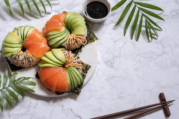 サーモンアボカドとキュウリの大理石のテーブルで寿司ドーナツ