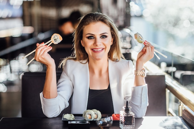 Sushi eating young caucasian  beautiful woman. healthy lifestyle female model smiling happy holding chopsticks sitting at table with plate of sushi in modern terrace.