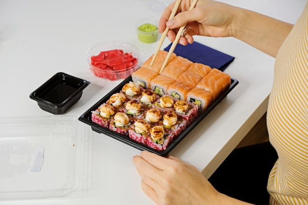 Sushi food delivery concept. woman eating philadelphia roll from plastic tableware