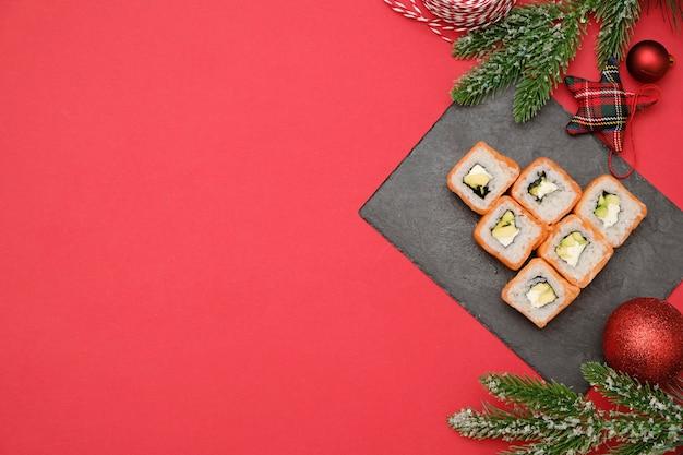 クリスマスのコンセプトの寿司。フィラデルフィアロールから作られた食用のクリスマスツリーは、装飾が施された赤い背景に転がります