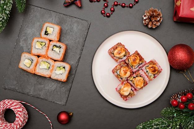 クリスマスのコンセプトの寿司。フィラデルフィアから作られた食用のクリスマスツリーは、黒い背景の上に転がります。