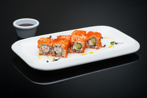 리플렉션 사용 하 여 검정색 배경에 접시에 초밥. 생선 롤