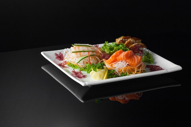 Суши в белой тарелке на темном фоне с отражением