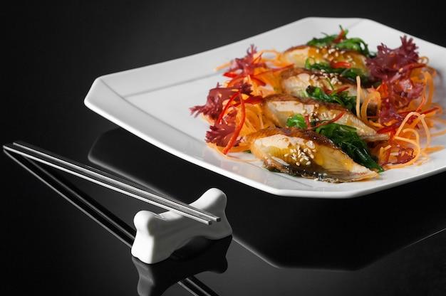 반사가 있는 검정색 배경에 젓가락이 있는 흰색 접시에 있는 스시