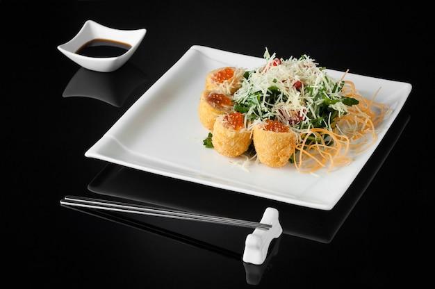 Суши в белой тарелке с соусником и палочками для еды на черном фоне с отражением