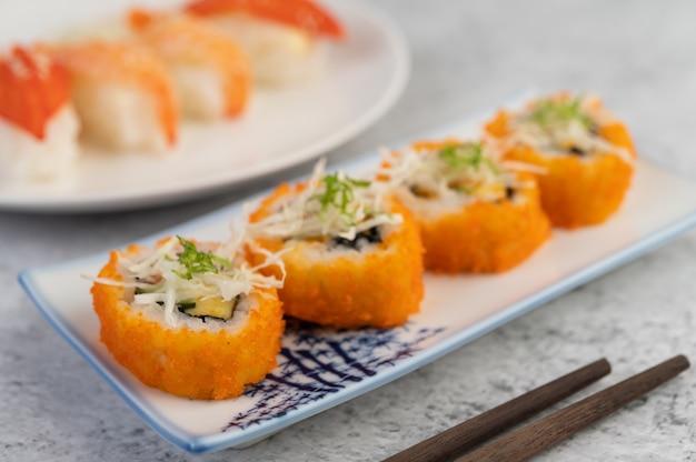 Суши в тарелке с палочками и соусом на белом цементном полу.