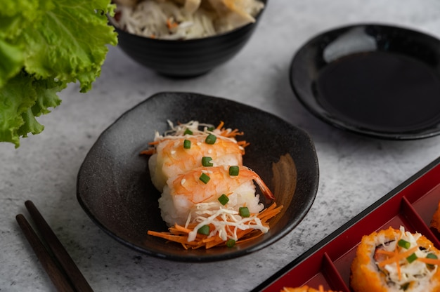 寿司は、白いセメントの床に箸とディップソースの入った皿にあります。