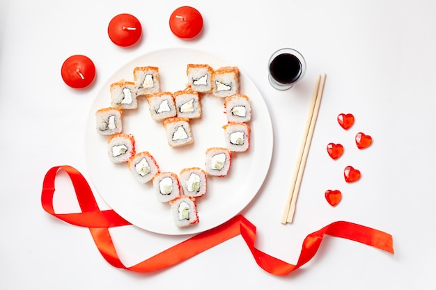 箸と醤油が入った白いテーブルの上に、ハートの形をした寿司が並べられています。