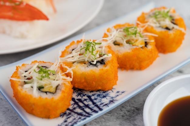 Il sushi è su un piatto con salsa di immersione su un pavimento di cemento bianco.