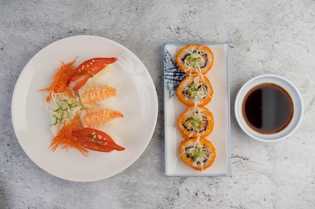 Sushi is on a plate with dipping sauce on a white cement floor.