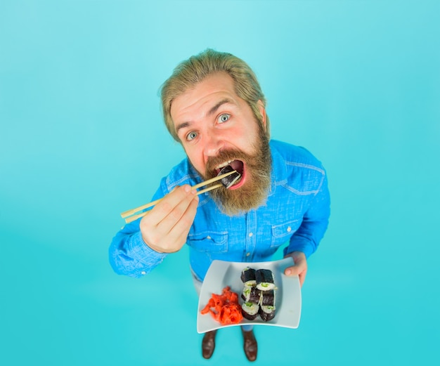 Sushi. japan. sushi delivery. japanese food. bearded man with plate of sushiroll. man eating sushi. man with sushi on chopstick. pickled ginger. plate of rolls. susi. exotic nutrition.
