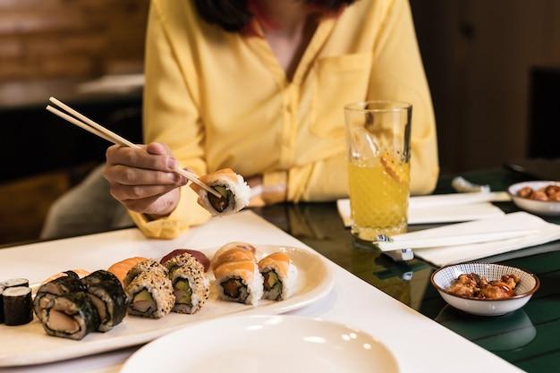レストランで女性の手で寿司日本食のクローズアップライフスタイル刺身おいしいシーフードとおにぎり今年の黄色