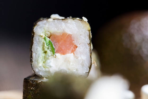 Sushi made from white rice, trout and avocado, ready-to-eat vegetable products and red fish salmon
