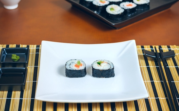 ソースと箸で皿に盛り付けられた寿司巻き巻き