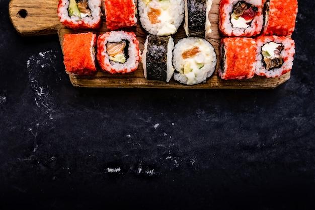 Набор суши-маки, подаваемый на деревянном планшете, съемка крупным планом сверху, японский азиатский ролл, пищевой композит ...