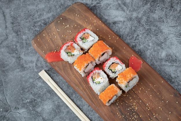 Sushi maki con caviale rosso e crema di formaggio su una tavola di legno.