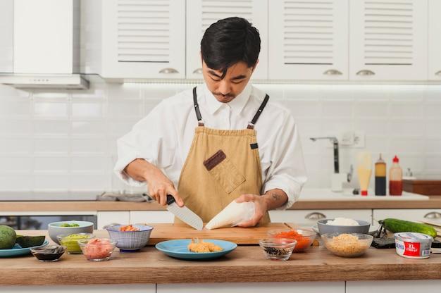 스시 마스터 요리사가 부엌에서 다양한 재료를 자르고 보드에 롤 만들기
