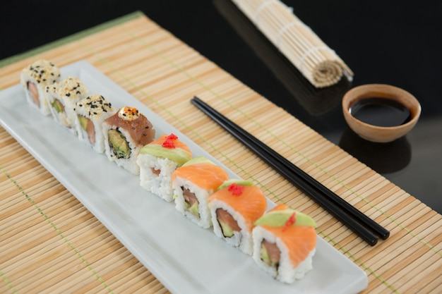 Sushi on mat with chopsticks