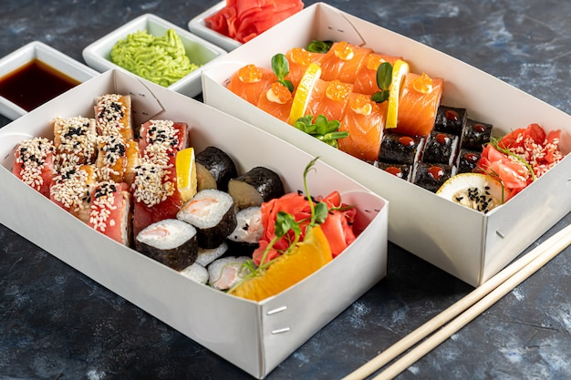 Меню суши в белой коробке перехода на деревянной предпосылке.