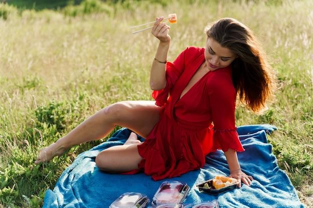 ピクニックで青い目の女の子の唇の近くの寿司。日本食レストランからの出前。ソーシャル ネットワークの広告。可愛い女の子が公園にあるお寿司を食べる。