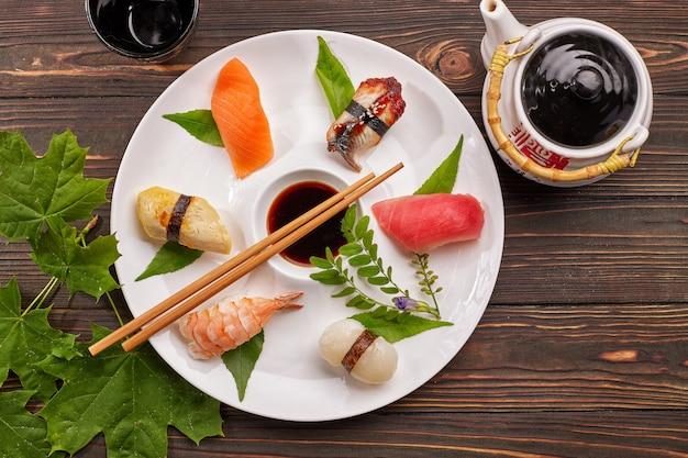 Суши нигири с тунцом, лососем, креветками, морским гребешком, угрем, омлетом, на белой тарелке с соевым соусом