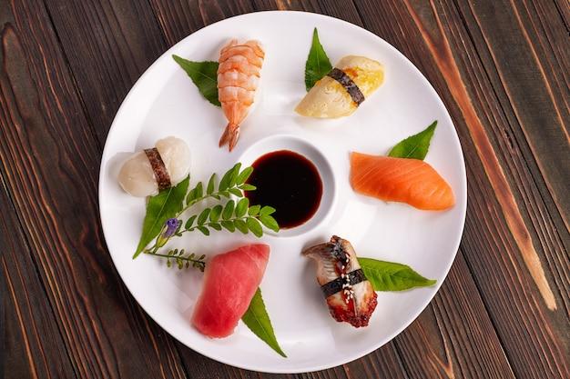 Суши нигири с тунцом, лососем, креветками, морским гребешком, угрем, омлетом, на белой тарелке