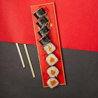 Sushi nori in red platter with wooden chopsticks.