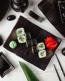 Sushi nori with ginger and wasabi in black plate.