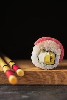 木の板に寿司。暗い背景に魚と一緒に転がります。